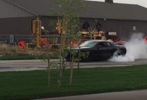 A 10-year-old kid rips off a burnout in a Dodge Challenger Hellcat