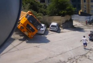 A truck rolls over and crushes some parked cars in Sochi, Russia