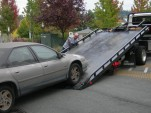 Car being loaded onto flat bed tow truck