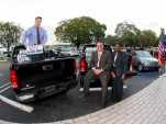GM representatives with GMC Sierras and supplies bound for Haiti