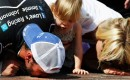 Jimmie, Genevieve Marie and Chandra Johnson kiss Indy's bricks - NASCAR photo