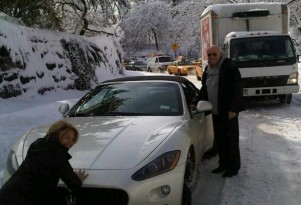 Katie Couric helps push Barry Diller's Maserati out of the snow