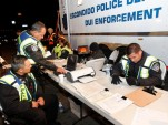 Police officers run identity checks at a sobriety checkpoint in Escondido, CA