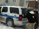 Rahm Emanuel helps push a police vehicle out of the snow
