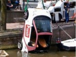 Smart ForTwo being hoisted out of Amsterdam canal, from De Telegraaf