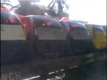 Tata Nanos shipped sideways on flatbed rail car outside Bangalore, India, from YouTube user Auroajay