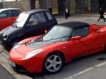 Tesla Roadster, Reva i, &amp; Ford Th!nk electric cars parked at charging station in Oslo, Norway