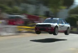 A BMW E30 with an E46 engine catches air during a hill climb event