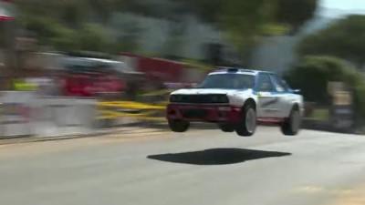 A BMW E30 with an E46 engine catches air during a hill climb event