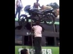 Amazing balance and strength as man climbs ladder with motorcycle on his head