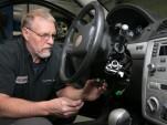 Gary Pittam performs recall service on a Chevrolet Cobalt Thursday, April 17, 2014